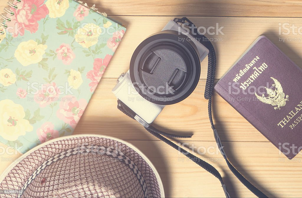 Camera and other travel objects on wooden background. stock photo