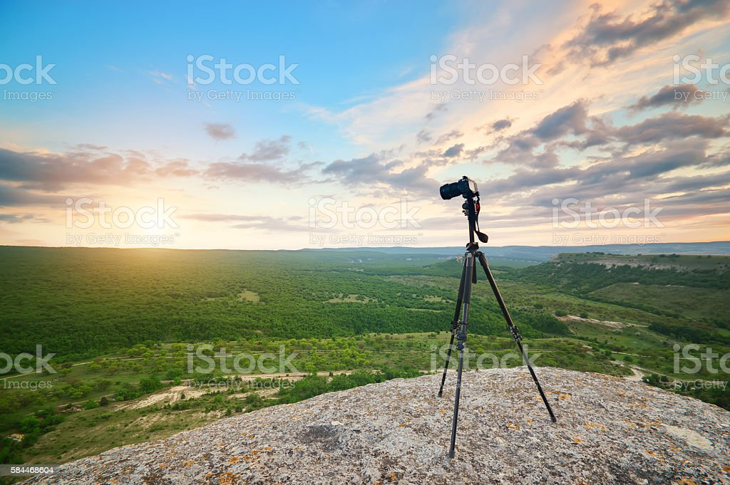 Camera and tripod on top mountain. stock photo