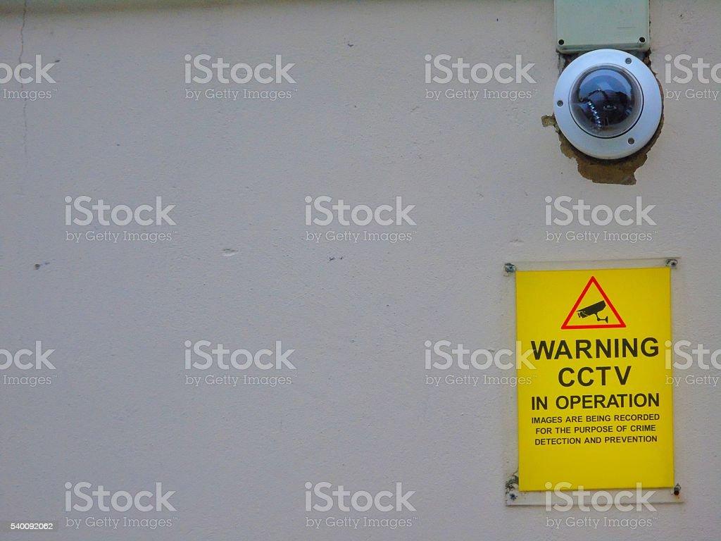 CCTV camera and warning sign stock photo