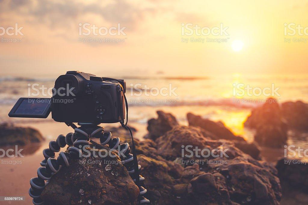 DSLR Camera capturing sunrise of beach view. stock photo