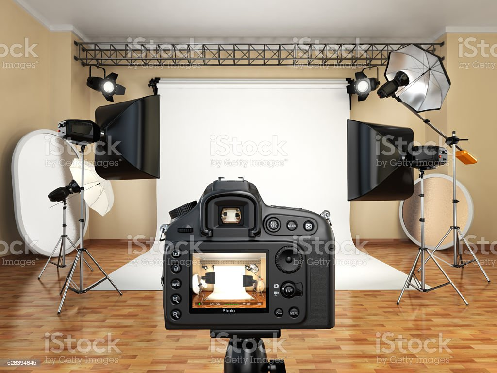 DSLR camera in photo studio with lighting equipment, softbox and stock photo