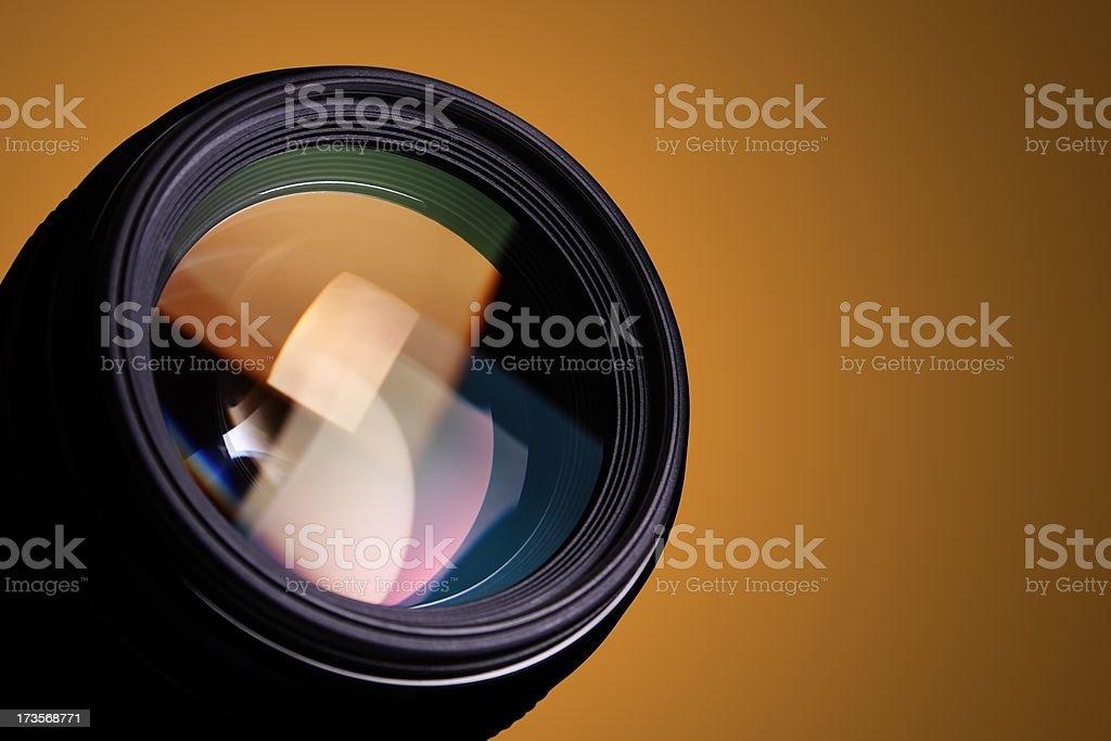 Camera lens and orange background royalty-free stock photo