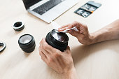 Camera lens cleaning with wet wipe, close-up