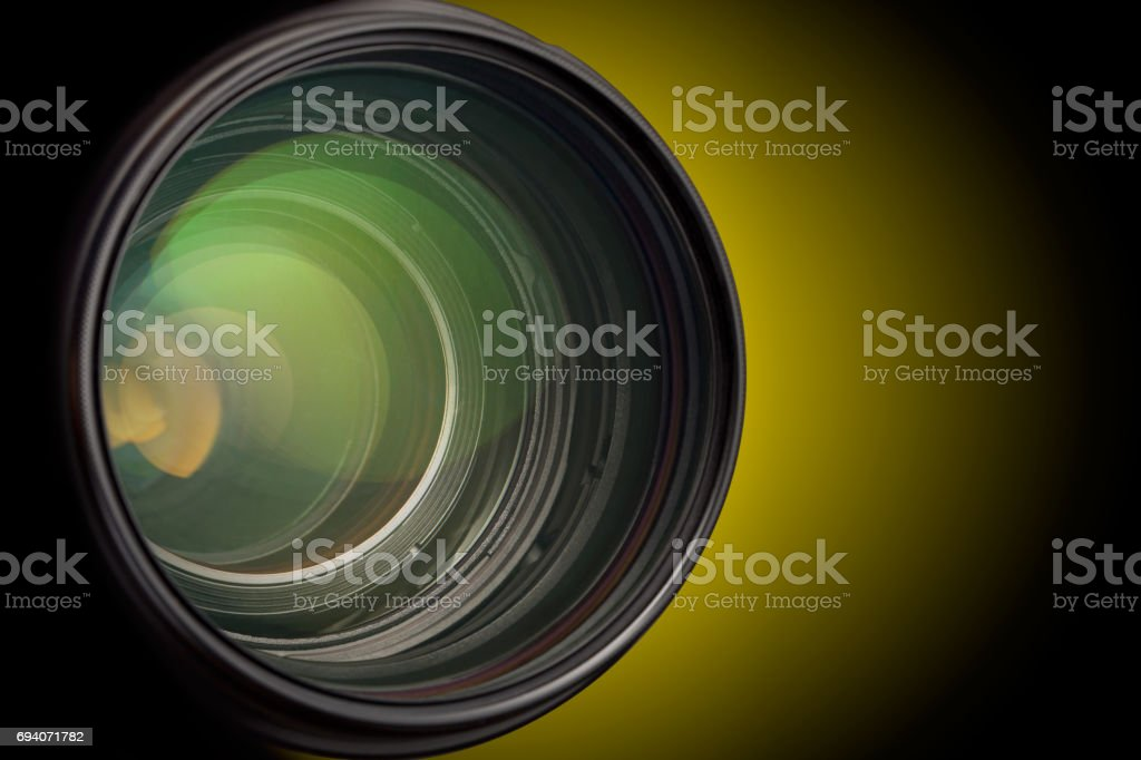 Camera lens close up isolated on dark background. stock photo