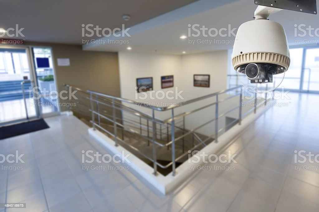 CCTV Camera Operating in side building with doors and stairs stock photo