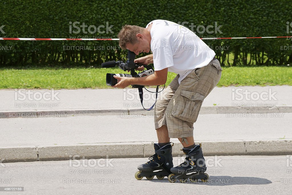 Camera operator with professional video-camera on roller skates royalty-free stock photo