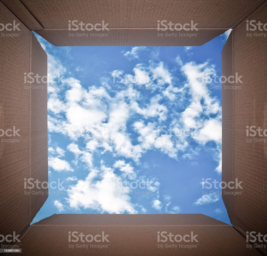 Camera Perspective inside cardboard box looking at blue sky stock photo