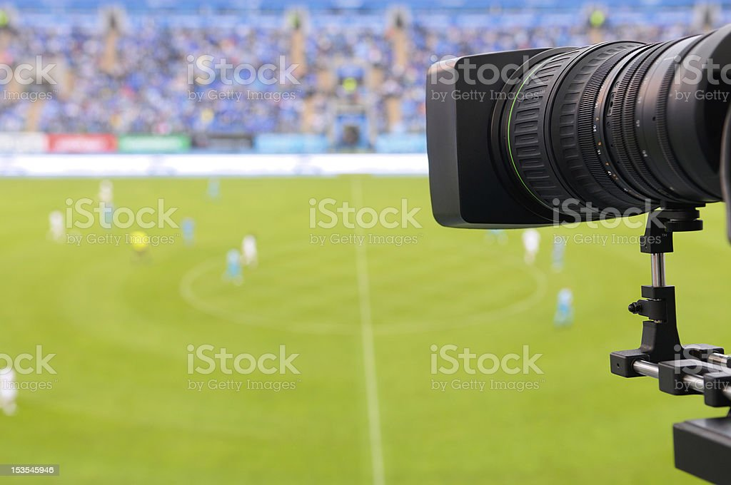 A camera recording a soccer game for television stock photo