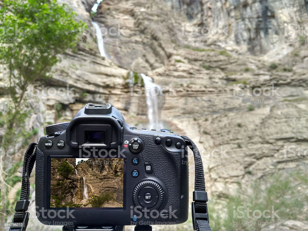 Camera taking photograph of waterfall stock photo