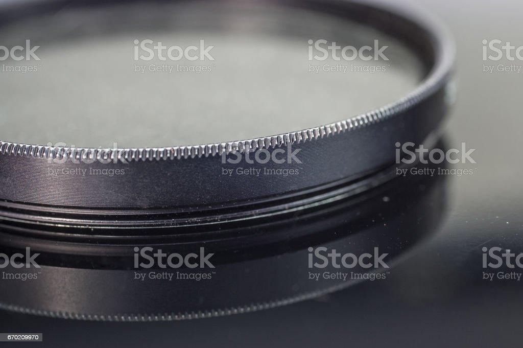 Camera UV Filter closeup on reflecting glass table stock photo