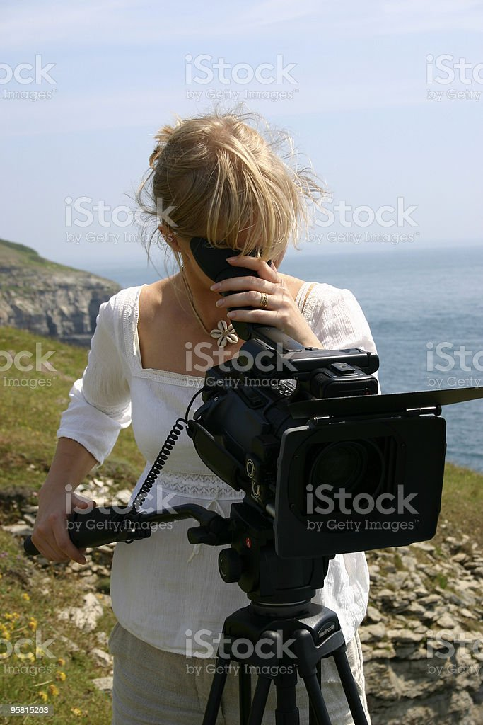 Camera woman at work filming outdoors royalty-free stock photo