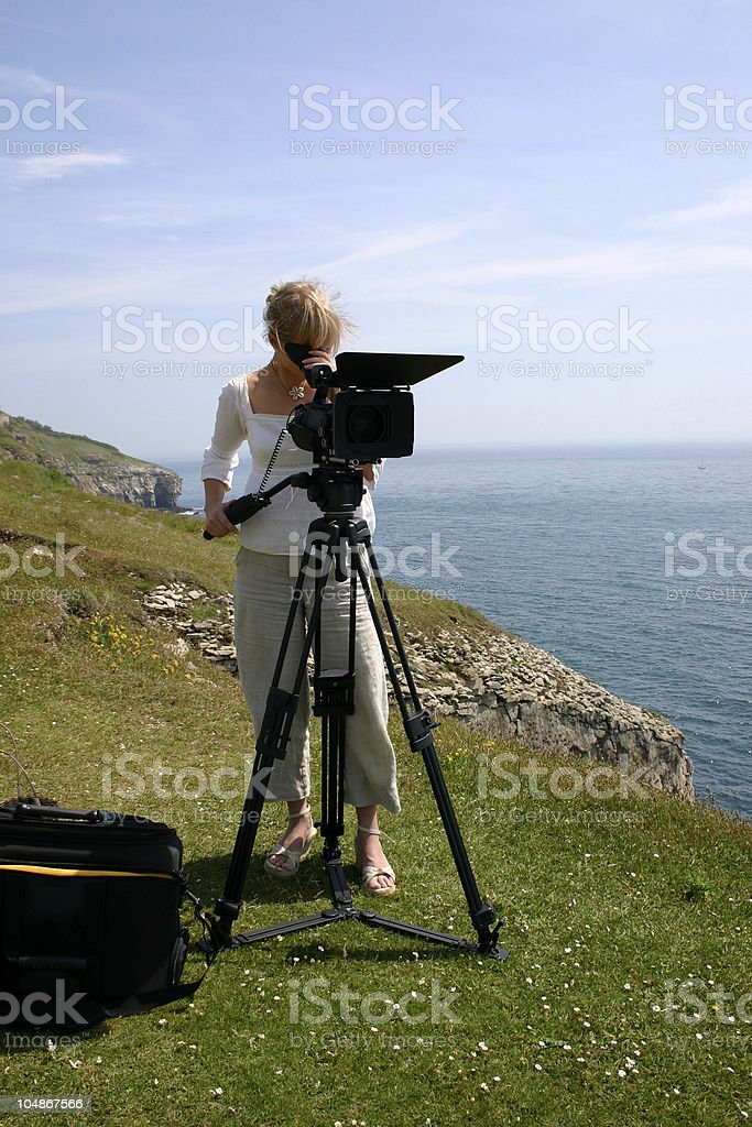 Camera woman at work, filming witha DV camera out in nature stock photo