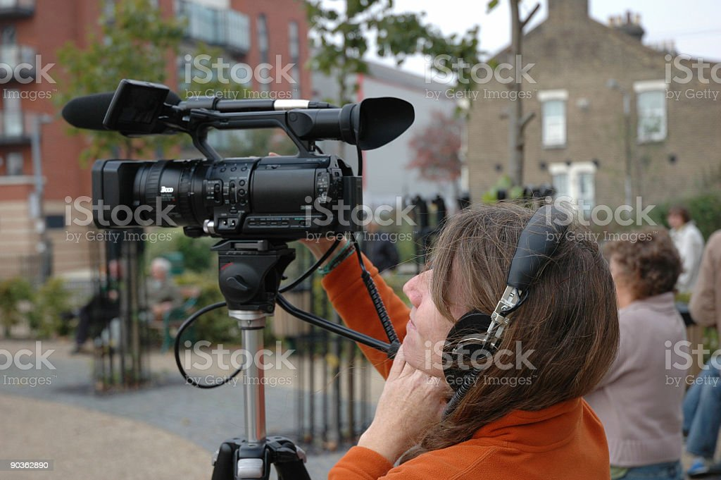 Camera woman with camera extended to get the shot royalty-free stock photo
