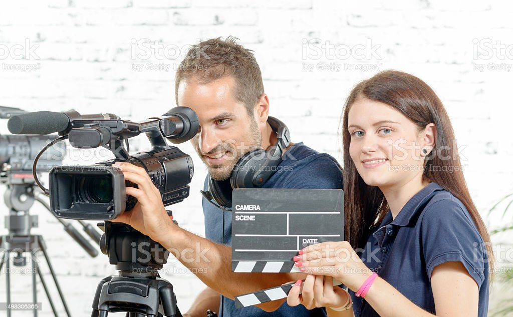cameraman and  young woman with a movie camera and clapper stock photo