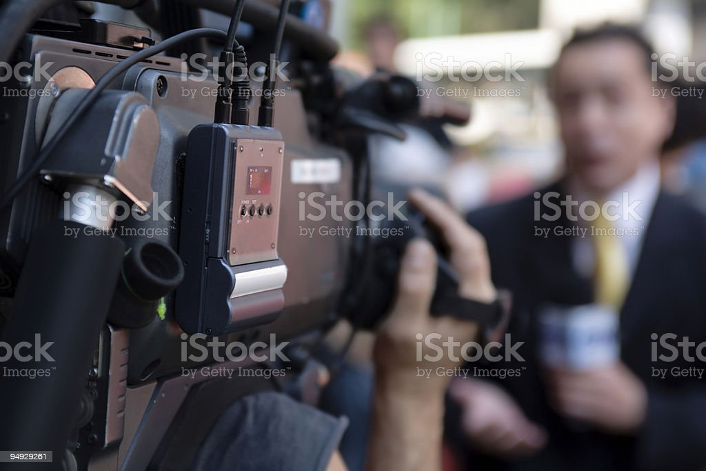 Cameraman filming a reporter stock photo
