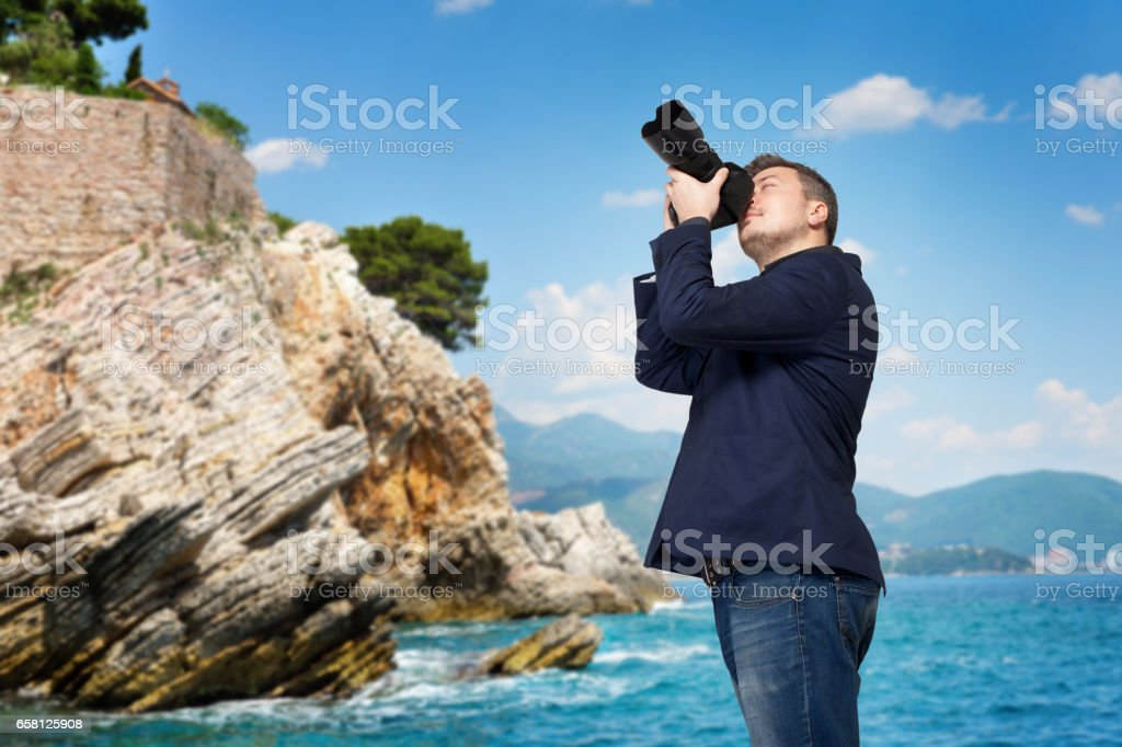 Cameraman in jacket with camera taking picture stock photo