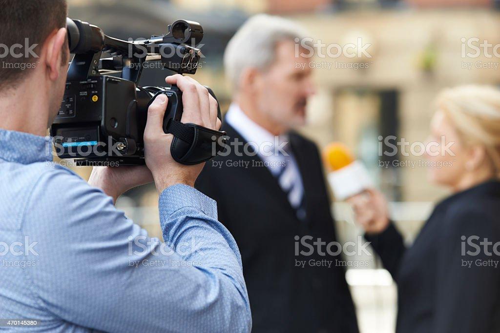 Cameraman Recording Female Journalist Interviewing Businessman stock photo