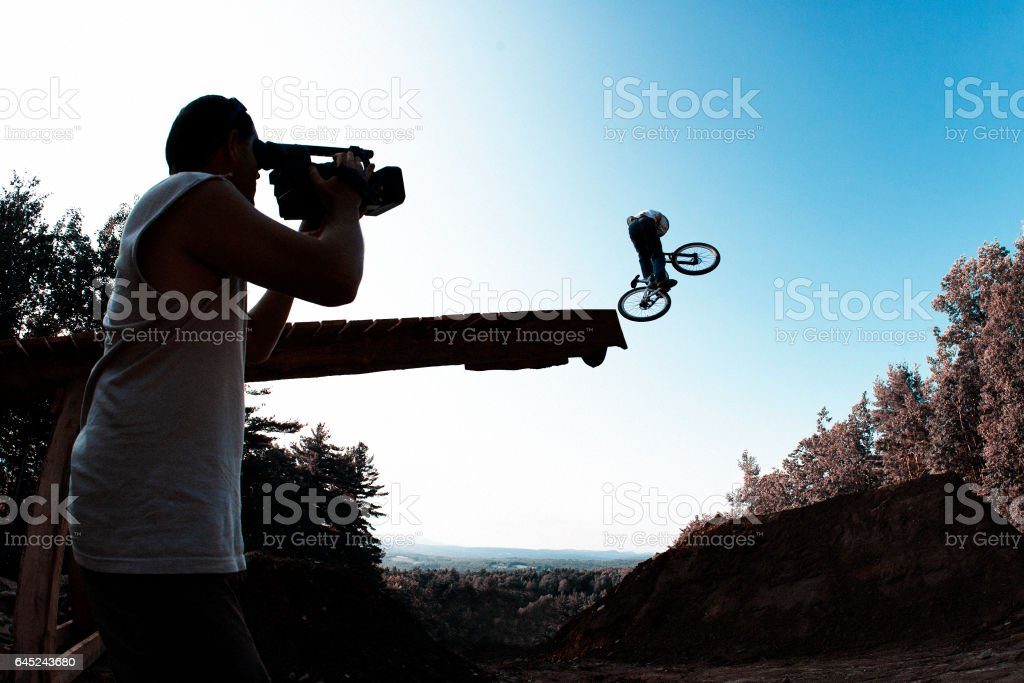 A cameraman shoots footage of a male mountain bike rider going off a wooden ramp jump at the end of the day. stock photo
