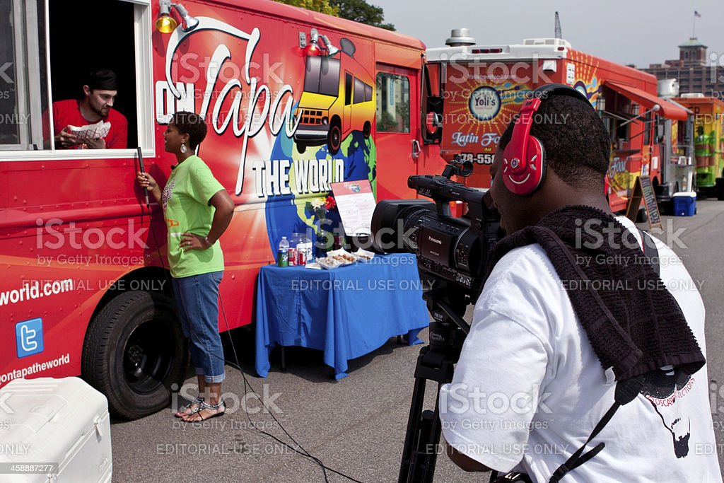 Cameraman Shoots Reporter Interviewing Food Truck Employee stock photo