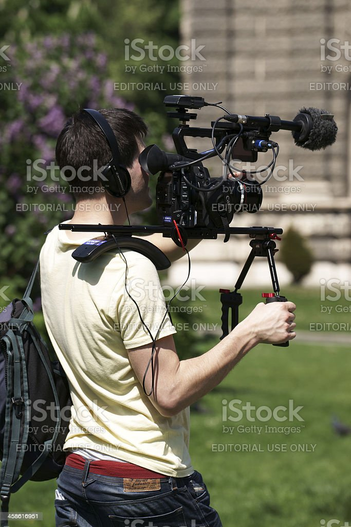 Cameraman with professional camera filming - vertical royalty-free stock photo