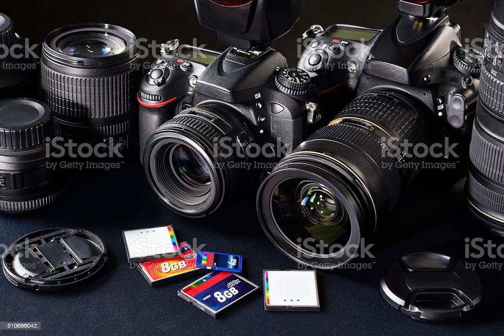 DSLR cameras, lens and flash cards stock photo