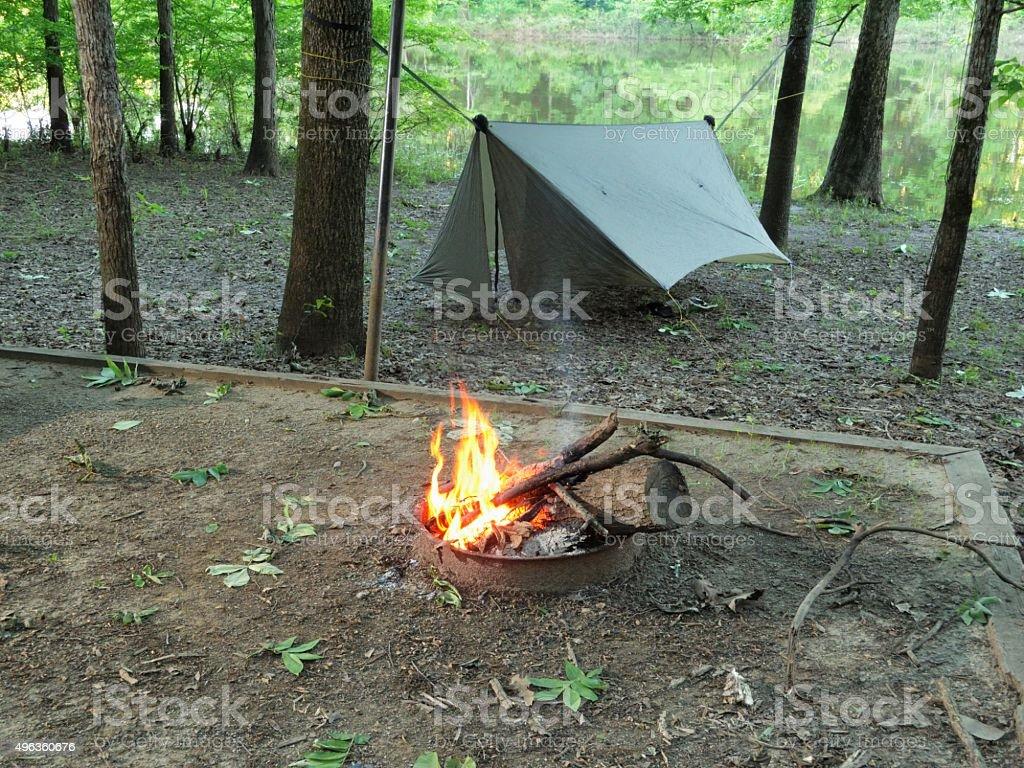 Camfire and modern camping hammock under tarp stock photo