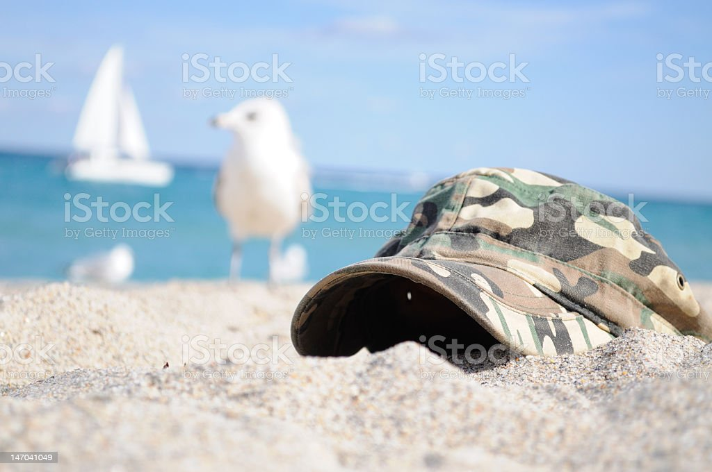 Camo hat at the beach royalty-free stock photo