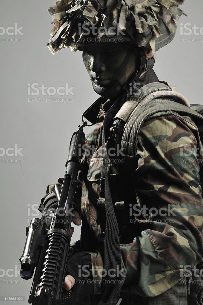 camouflaged soldier with weapon looking serious and ready royalty-free stock photo