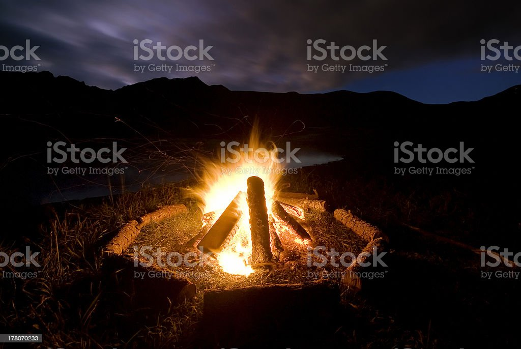 Camp fire beside lake and mountains. stock photo