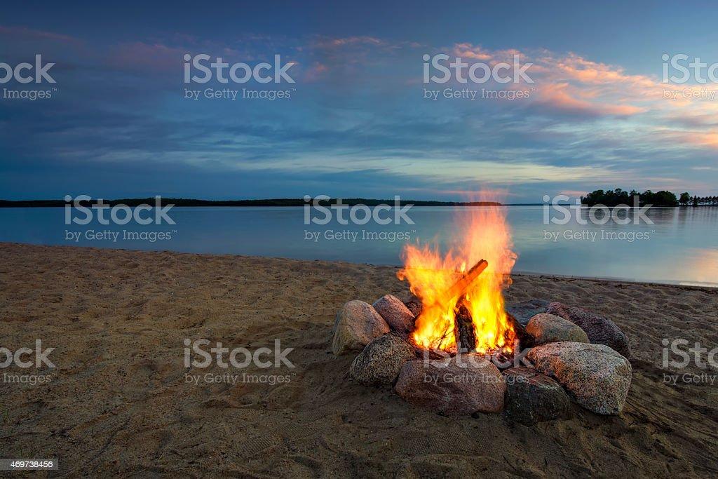 Camp fire, beside lake at sunset. Minnesota, USA stock photo