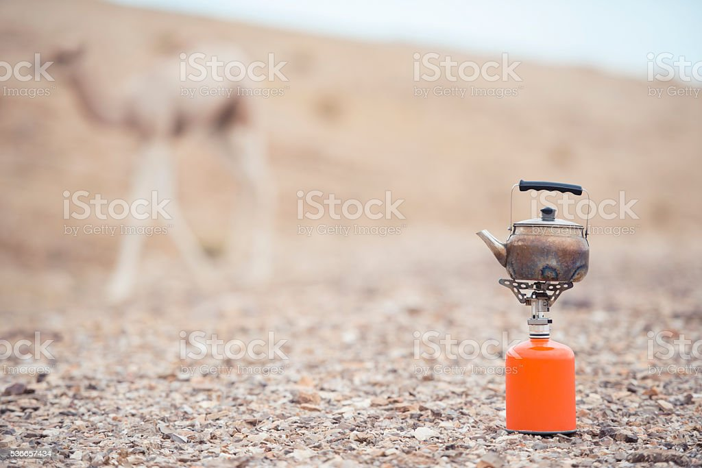 Camp gas stove with kettle on desert ground. stock photo