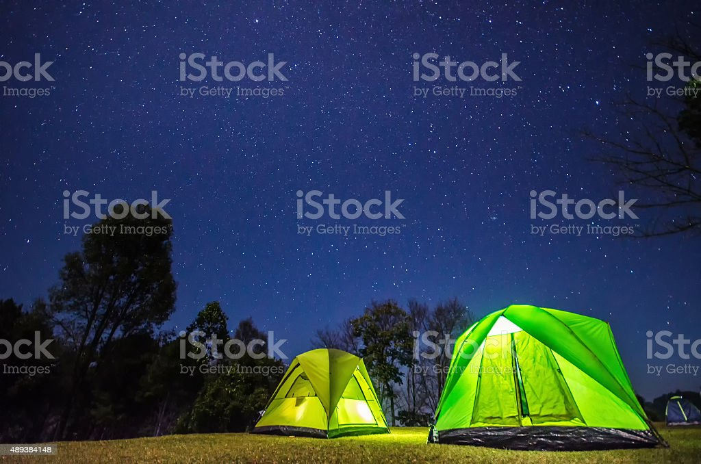 camp in forest at night with star stock photo
