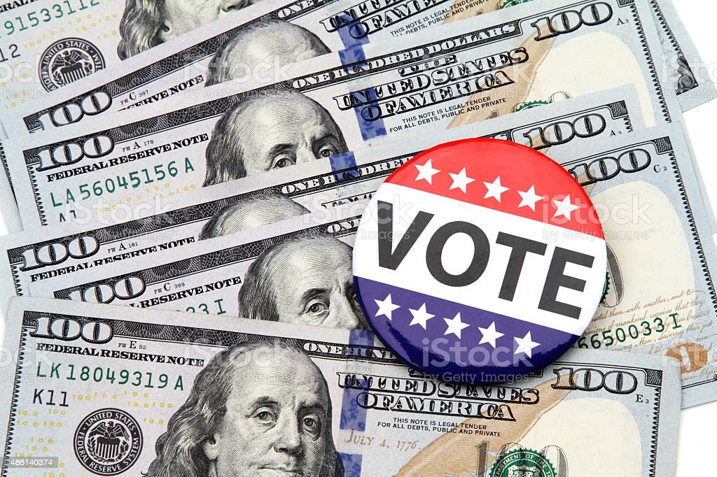 VOTE campaign button on top of hundred dollar bills stock photo