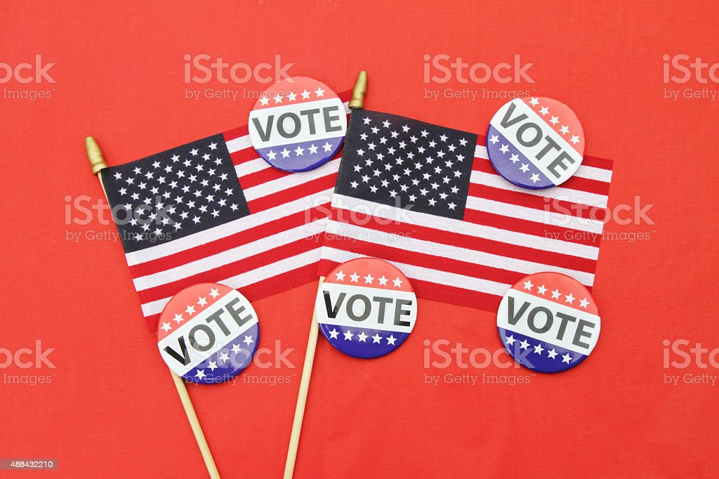 VOTE campaign buttons and USA flags on red stock photo