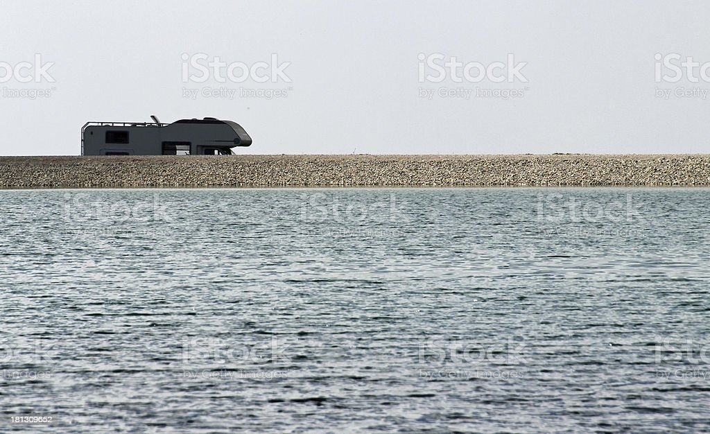 camper parked on the Bank of an alpine lake royalty-free stock photo