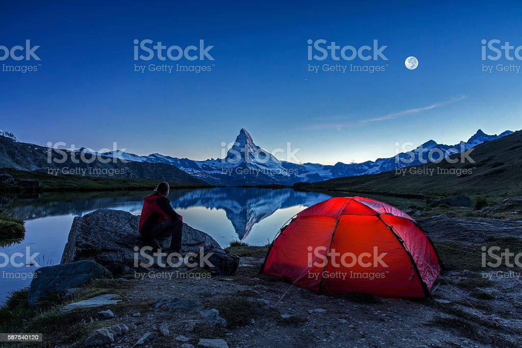 Camper under full Moon at Matterhorn stock photo