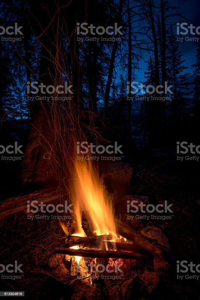 Campfire and sparks against blue sky of night stock photo