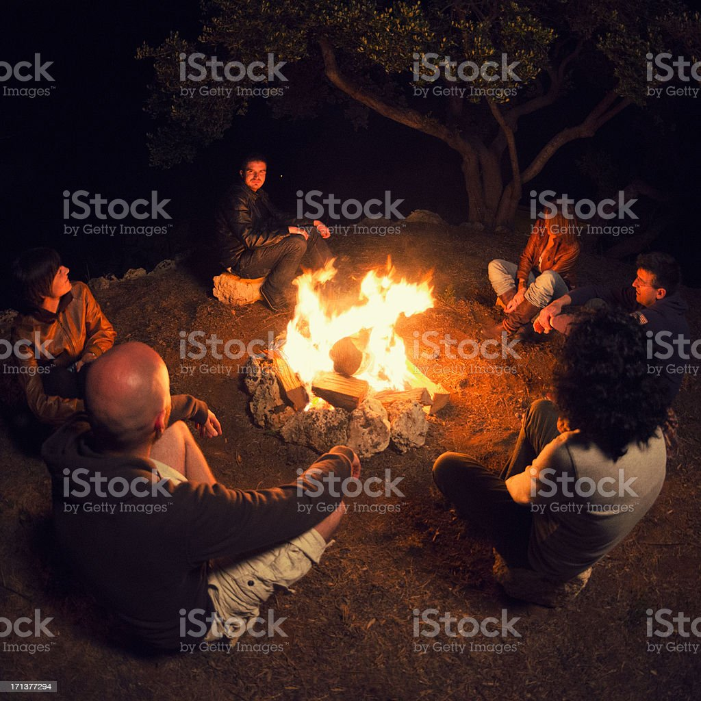Campfire of friends in circle on the fire stock photo