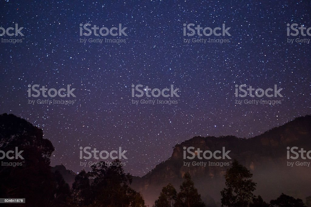 campfire smoke and starry skies stock photo