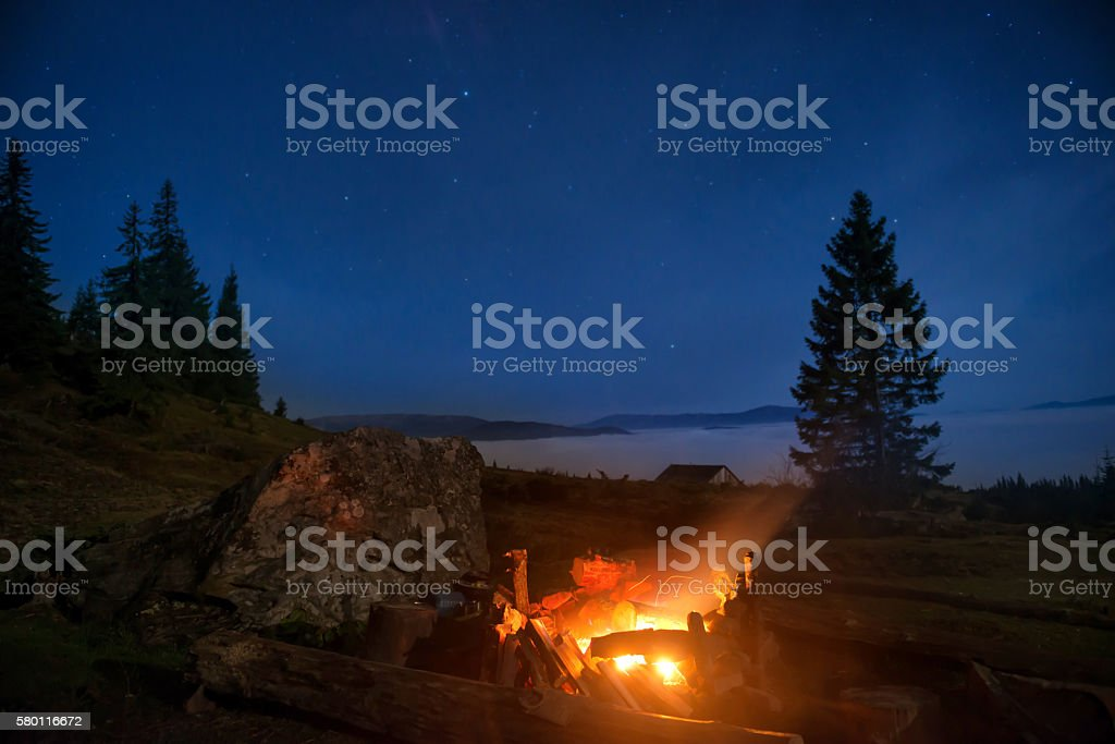 Campfire under blue night sky stock photo