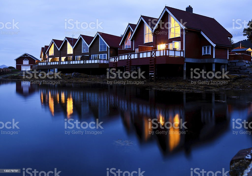 Camping cabins on a fjord at night stock photo