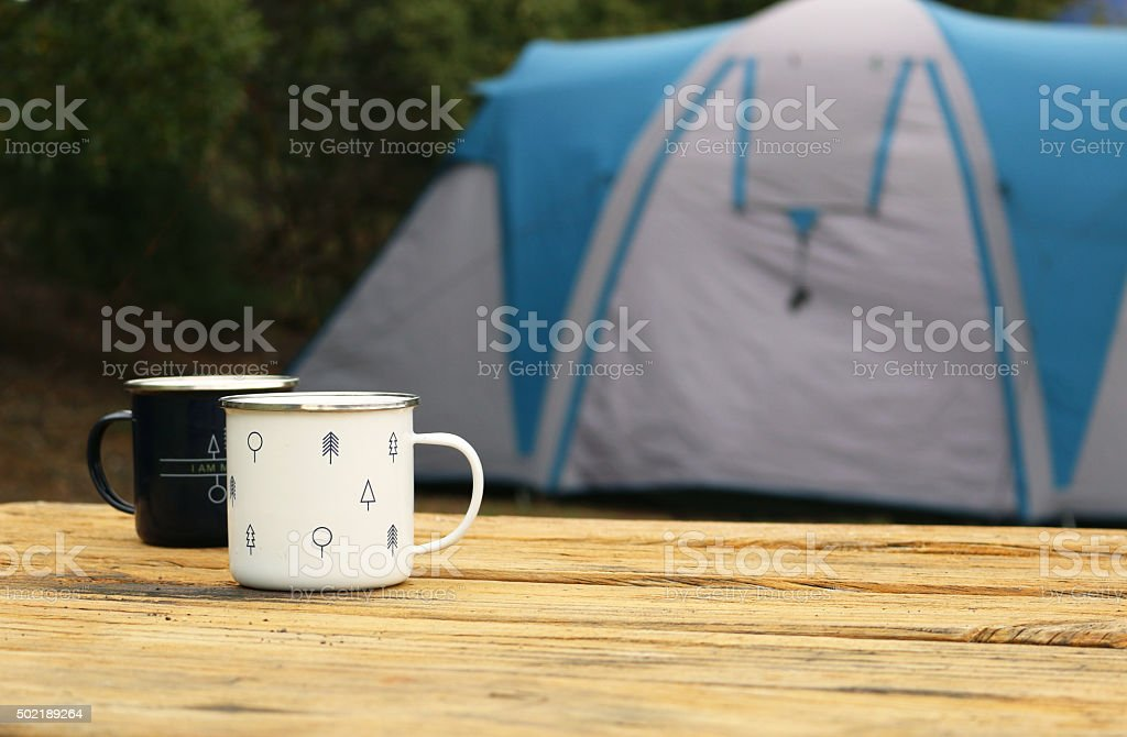 Camping cups and tent stock photo