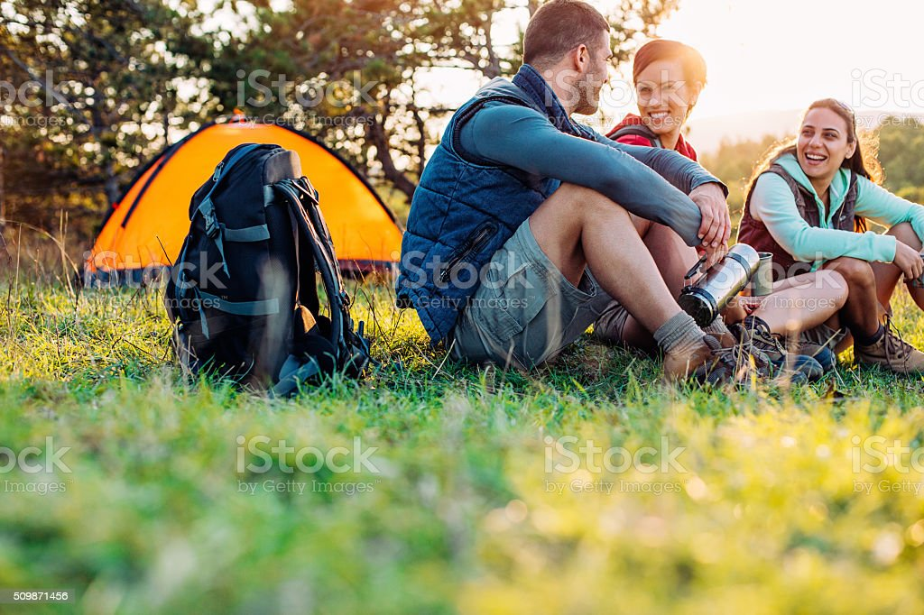 Camping friends at sunset stock photo