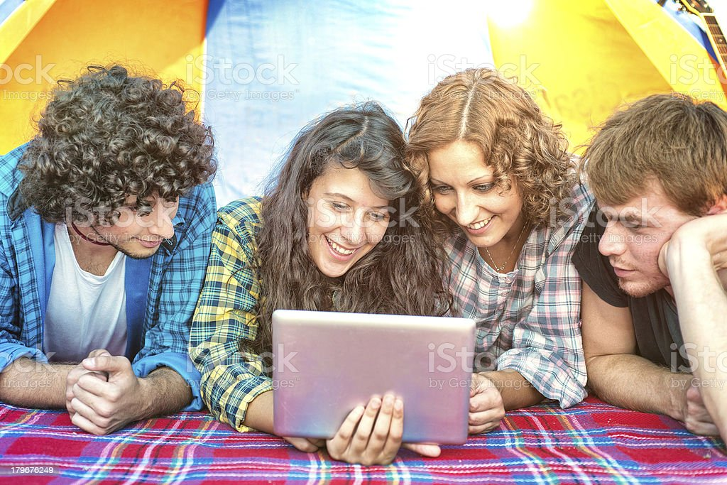 Camping: Friends Looking Tablet in a Tent royalty-free stock photo