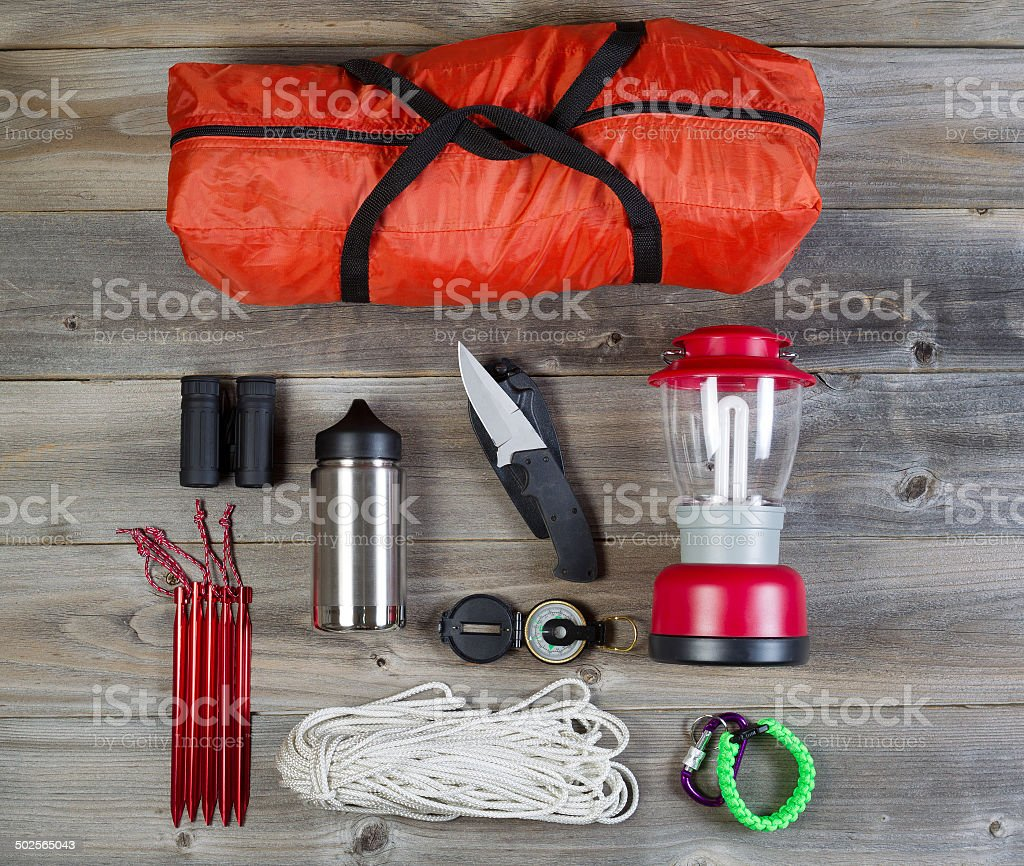 Camping Gear on Rustic Wooden Boards stock photo