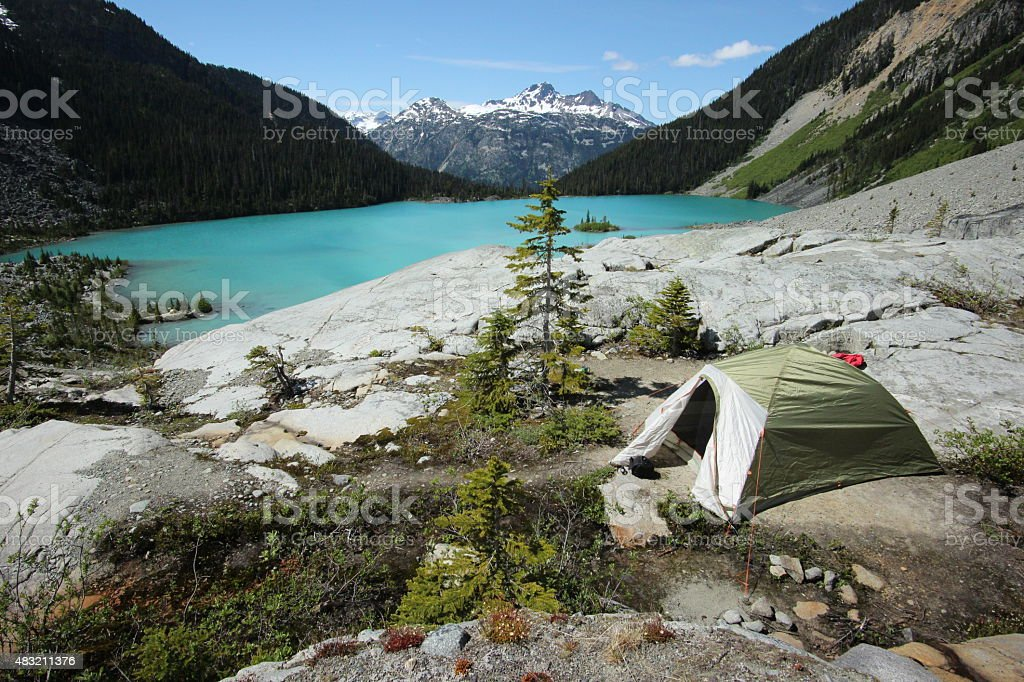 Camping in front of a beautiful lake surrounded by mountains stock photo