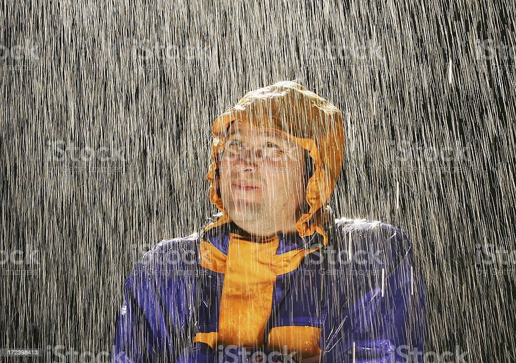 A man in a waterproof jacket looks up to the sky as he stands in the...