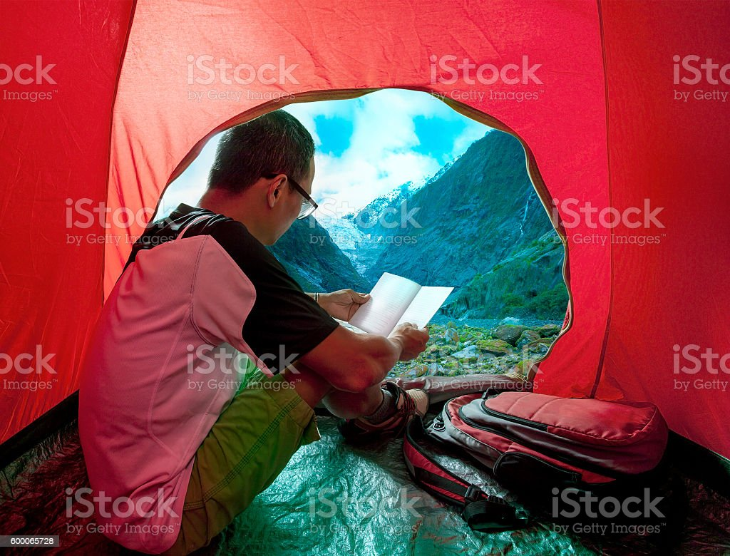 camping man reading a traveling guild book in camp stock photo