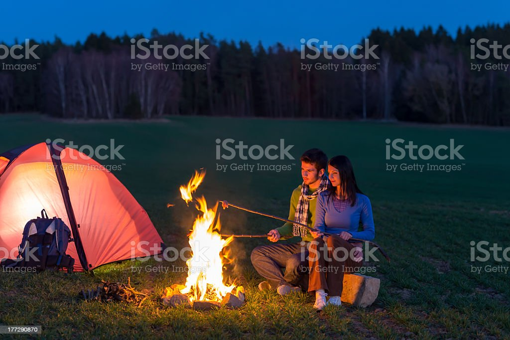 Camping night couple cook by campfire romantic royalty-free stock photo