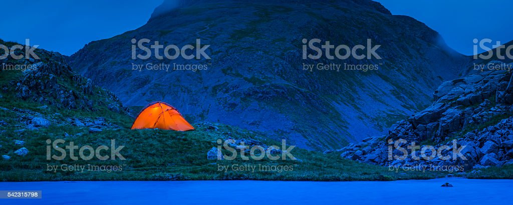 Camping tent illuminated against blue dusk mountains panorama Lake District stock photo
